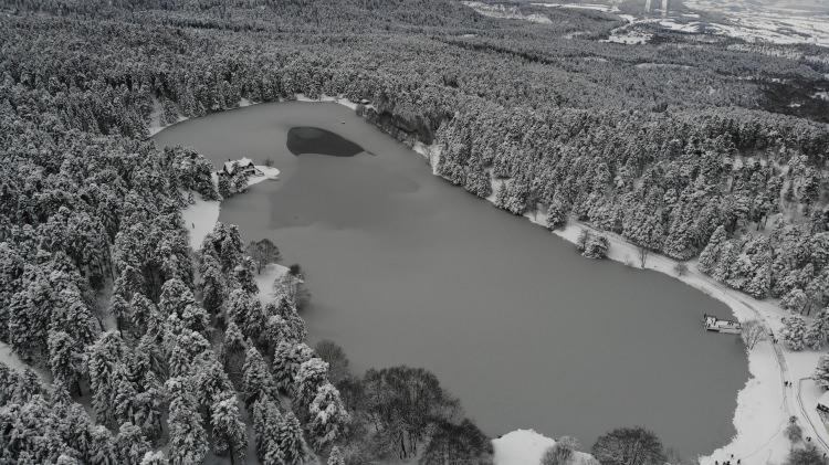 <p>Yılın 4 mevsimi yurtiçi ve yurtdışından binlerce tatilcinin tercih ettiği Gölcük Tabiat Parkı'nın çevresinde bulunan çam ağaçlarının karla kaplı muhteşem manzarası havadan görüntülendi. Hava sıcaklığının sıfırın altında eksi 20 derecelere kadar düşmesi sonrası buz tutan gölün ormanla bütünleştiği görüntüler tatilcileri mest etti.</p>