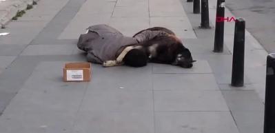 Sokak ortasında köpeğe sarılarak uyuyor