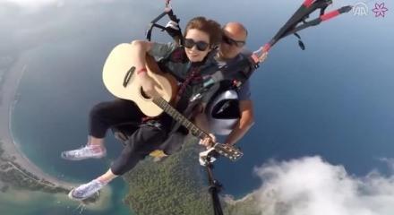 Paraşütle atlarken gitar çalan çılgın kadın fenomen oldu!