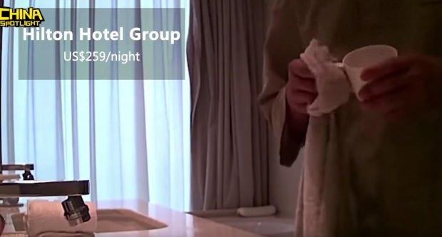 Temizlik görevlisi banyoyu sildiği havluyla bardak siliyor.