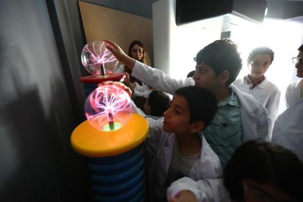 Öğrenciler bilim merkezinde deney yapıyor.