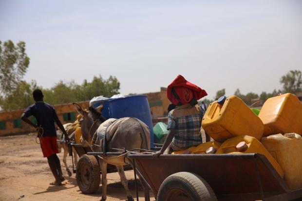 Eşeklerin çektiği arabalar ile su almaya giden çocuklar
