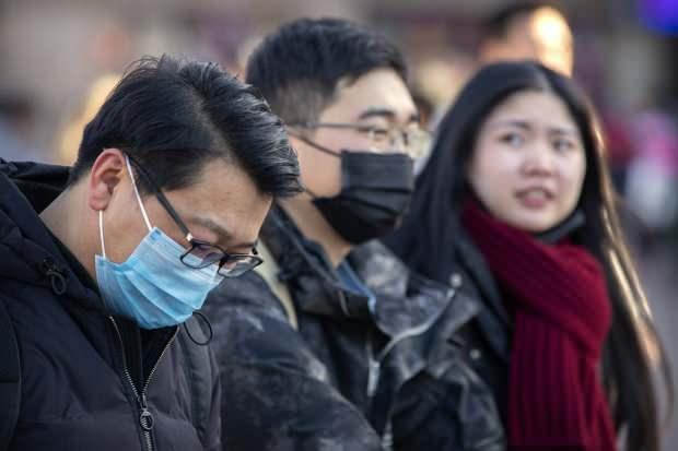 Çinde yayılan virüsten korunmak için maske kullanan insanlar
